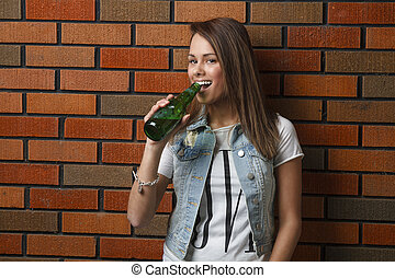 Drinking a beer - twenty something girl leaning against wall...