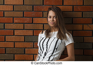 Young woman - twenty something girl leaning against a brick...