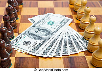 US dollars and chess figures on an old wooden chessboard