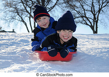 Two young boys sledding downhill together - Two little boys...