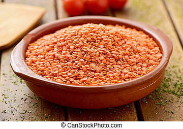 uncooked red lentils in an earthenware bowl - closeup of an...