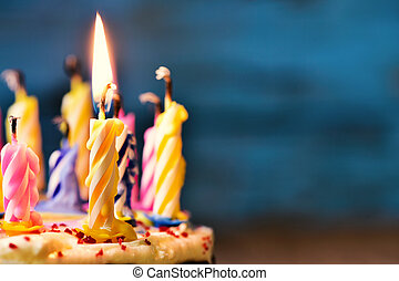 blowing out the candles of a cake - closeup of some unlit...