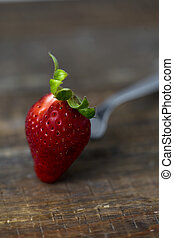strawberry on a wooden table - closeup of a ripe strawberry...