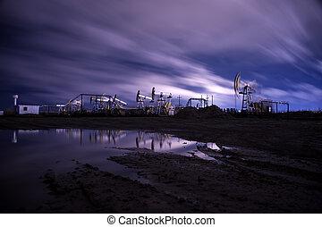 Oil pumps. - Oil pump jacks at sunset sky background. Toned.