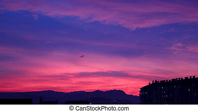 Sunset, cloudy sky background above night city Nature