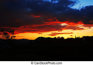 Sunset, cloudy sky background over night city Nature