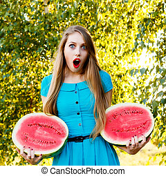 Beautiful blonde girl holding two halves of a sliced...