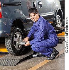 Mechanic Fixing Car Tire With Pneumatic Wrench - Portrait of...