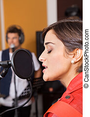 Woman With Eyes Closed Singing In Studio - Young woman with...