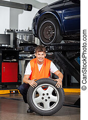 Happy Mechanic Holding Tire At Repair Shop - Portrait of...