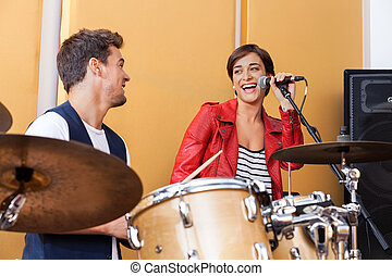Female Singer Performing While Looking At Male Drummer