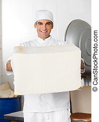 Confident Male Baker Holding Big Bread Loaf - Portrait of...