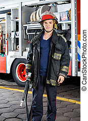 Confident Firefighter Holding Hose Against Truck - Portrait...