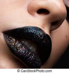 Brilliant glossy lips closeup. Purple glitter on black lipstick
