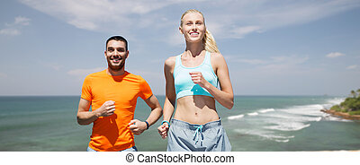 happy couple running over sea or beach background - fitness,...