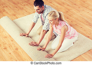 happy couple unrolling carpet or rug at home - people,...