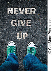 Never give up - Brand new green shoes from above on asphalt...