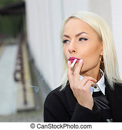 Portrait of a business woman nervously smoking