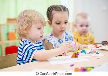 kids doing arts and crafts in kindergarten - kids modeling...