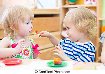 two kids playing in kindergarten together - kids group...