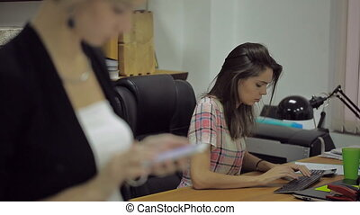 Young woman quickly typing on a keyboard, in the foreground girl sends a message from smartphone