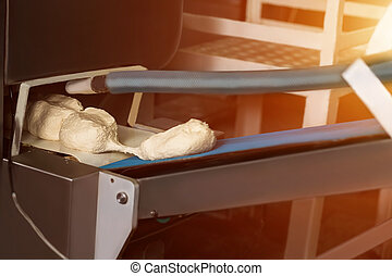 Dough pieces on conveyor belt. Machine separates pieces of...