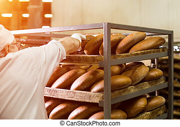 Brown bread on wooden rack. Worker touching bread on rack....