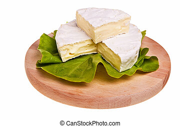 Round camembert cheese on lettuce on cutting board.