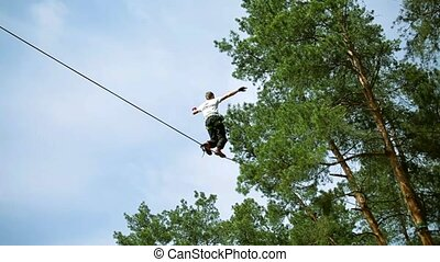 man walking on a rope over an abyss and balances - man...