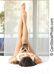 Woman with perfect waxed legs with smart phone - Woman with...