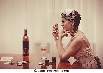 Woman in veil is playing poker with the glass of whiskey....