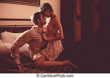Beautiful couple is kissing in the bedroom
