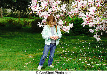 Preschooler girl playing with magnolia flowers
