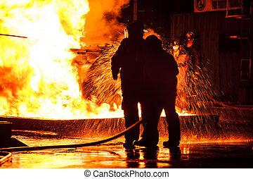 Firemen using water hose on raging fire