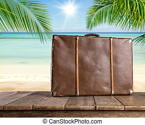 Old travel suitcase on wooden planks, tropical beach on...