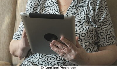 An old woman viewing photos using a digital tablet - The old...