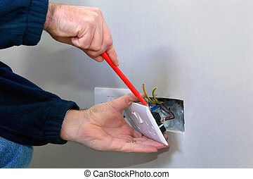 Electrician installing a socket - The hands of an...