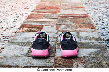 Running shoes in home garden foot path