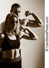 Guy and girl flex biceps Muscular couple flexing arms Show...