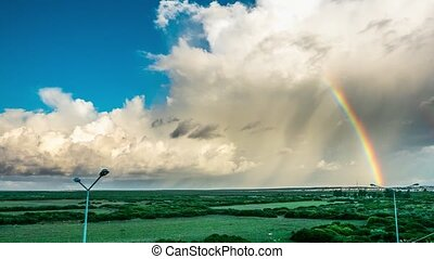 Rainbow, green field and clouds on the sky. 4k, Time lapse....