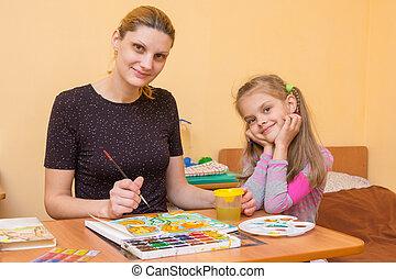 a drawing teacher teaches a little girl paint watercolors