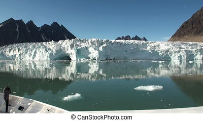 Sea mountains and large icebergs reflecting water.