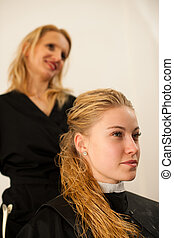 Hair stylist at work - hairdresser  and  customer evaluating hair after haircut and before doing hairstyle in a professional salon