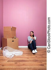 Woman having a break from packing for her home move