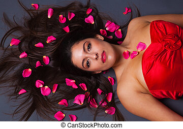 Beautiful brunette with rose petals in her hair