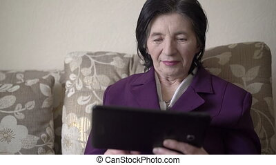 Mature business woman sitting on a sofa, using a tablet and sincerely smiling
