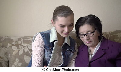 Young girl learning older woman how to use tablet - Young...