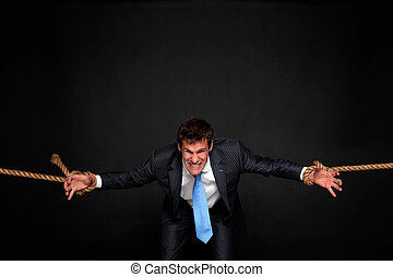 Businessman being pulled by rope on both sides. -...