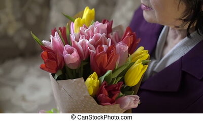 Close up profile of old woman holding a bouquet of tulips and smiling. Slowly