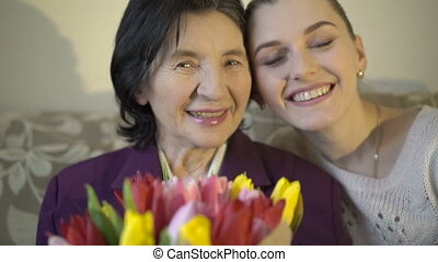 Gandmother with flowers and granddaughter smiling on the...